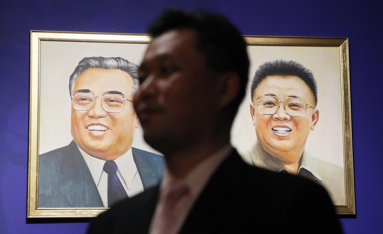 "A DPRK official speaks to the media in front of portraits of North Korean leaders Kim Il-sung and Kim Jong-il at the ""Made In North Korea"" exhibition held at the UMAM museum in Moscow, Russia January 20, 2018. REUTERS/Maxim Shemetov"