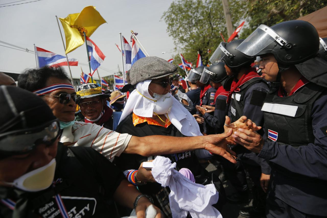 Policemen and anti-government protesters greet each other inside the compound of the metropolitan police headquarters, the site of fierce clashes over the last few days, in Bangkok December 3, 2013. Thailand's government ordered police to stand down and allow protesters into state buildings on Tuesday, removing a flashpoint for clashes and effectively bringing an end to days of violence in Bangkok in which five people have died. REUTERS/Damir Sagolj (THAILAND - Tags: SOCIETY CIVIL UNREST POLITICS)
