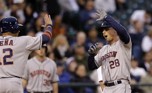Houston Astros' Rick Ankiel (28) is greeted at home by Carlos Pena on his two-run home run against the Seattle Mariners in the second inning of a baseball game Wednesday, April 10, 2013, in Seattle. (AP Photo/Elaine Thompson)