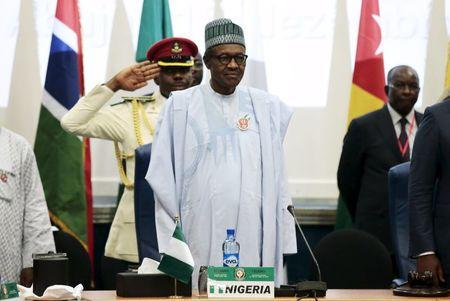 Nigeria's President Muhammadu Buhari stands at the opening of the 48th ordinary session of ECOWAS Authority of Head of States and Government in Abuja
