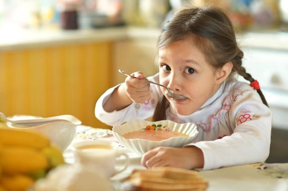 Girl eating bowl of soup at the kitchen table.