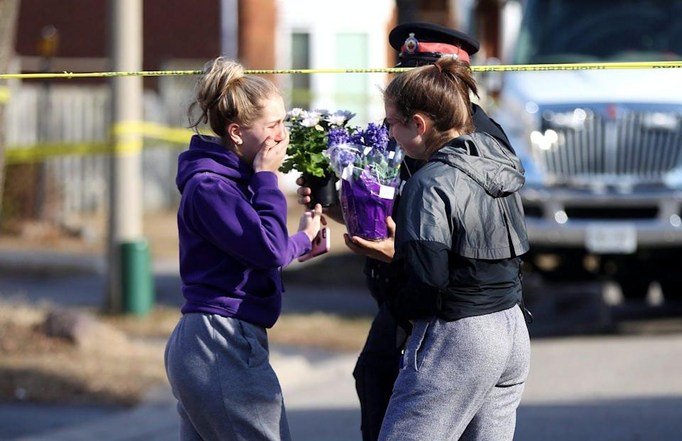 """<span class=""""caption"""">Two teenaged girls hand over flowers in Ajax, Ont., in March 2015 to a police officer in a show of sympathy for the victims of a triple slaying, a mother and her two children. The woman's domestic partner was charged in the crime and goes to trial soon.</span> <span class=""""attribution""""><span class=""""source"""">THE CANADIAN PRESS/Colin Perkel </span></span>"""