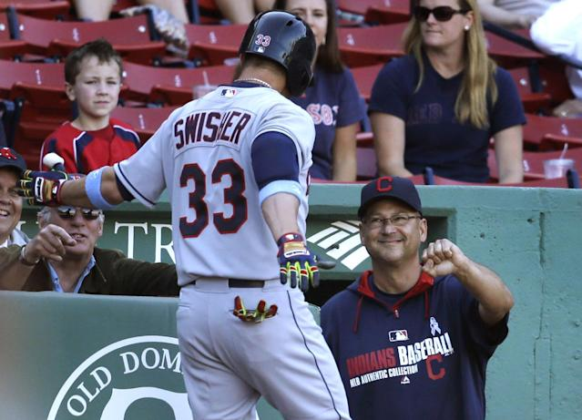 Cleveland Indians' Nick Swisher, left, is welcomed to the dugout by Indians manager Terry Francona right, after hitting a home run in the 11th inning of a baseball game against the Boston Red Sox, Sunday, June 15, 2014, in Boston. The Indians won 3-2 in 11 innings. (AP Photo/Steven Senne)
