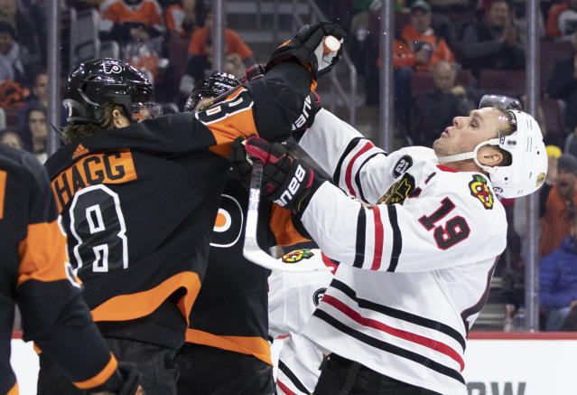 Chicago Blackhawks' Jonathan Toews, right, tangles up with Philadelphia Flyers' Robert Hagg, left, of Sweden, during the third period of an NHL hockey game, Saturday, Nov. 10, 2018, in Philadelphia. The Flyers won 4-0. (AP Photo/Chris Szagola)