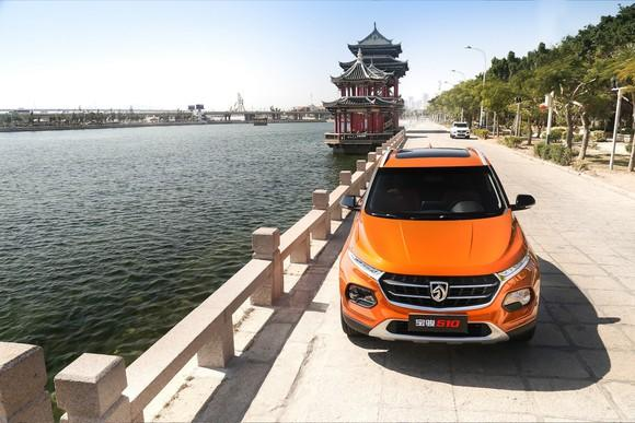An orange Baojun 510, a compact crossover SUV, parked on a waterfront road in China.