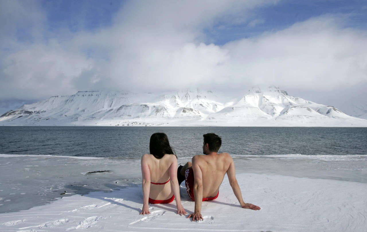"""Climate activists Lesley Butler and Rob Bell (R) """"sunbathe"""" on the edge of a frozen fjord in the Norwegian Arctic town of Longyearbyen April 25, 2007. The activists are warning that global warming could thaw the Arctic and make the sea warm enough for people to swim and sunbathe in.     REUTERS/Francois Lenoir   (NORWAY)  BEST QUALITY AVAILABLE"""