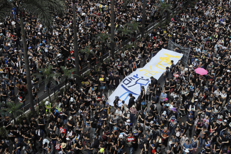 "Tens of thousands of protesters march through the streets with a banner reading ""Hong Kong say No"" as they continue to protest an extradition bill, Sunday, June 16, 2019, in Hong Kong. Hong Kong residents Sunday continued their massive protest over an unpopular extradition bill that has highlighted the territory's apprehension about relations with mainland China, a week after the crisis brought as many as 1 million into the streets. (AP Photo/Kin Cheung)"