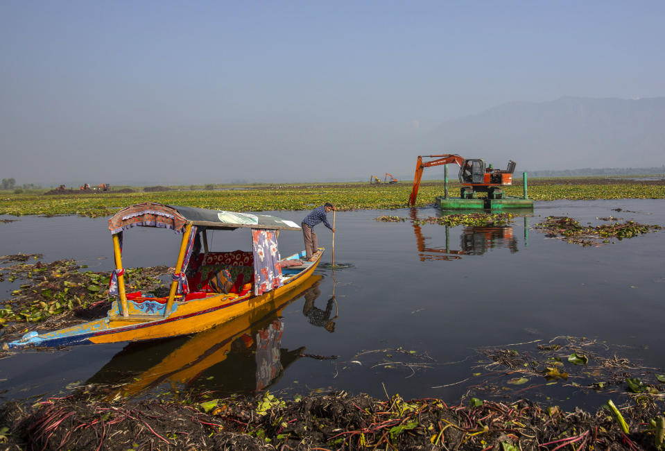A Kashmiri boatman rows his boat as a de-weeding machine works at Dal lake in Srinagar, Indian controlled Kashmir, Tuesday, Sept. 14, 2021. Weeds, silt and untreated sewage are increasingly choking the sprawling scenic lake, which dominates the city and draws tens of thousands of tourists each year. (AP Photo/Mukhtar Khan)