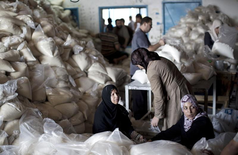 Palestinian women wait sitting amidst bags of sugar stored at a distribution centre of the United Nations Relief and Works Agency (UNRWA) in Gaza City on August 11, 2014 (AFP Photo/Mahmud Hams)