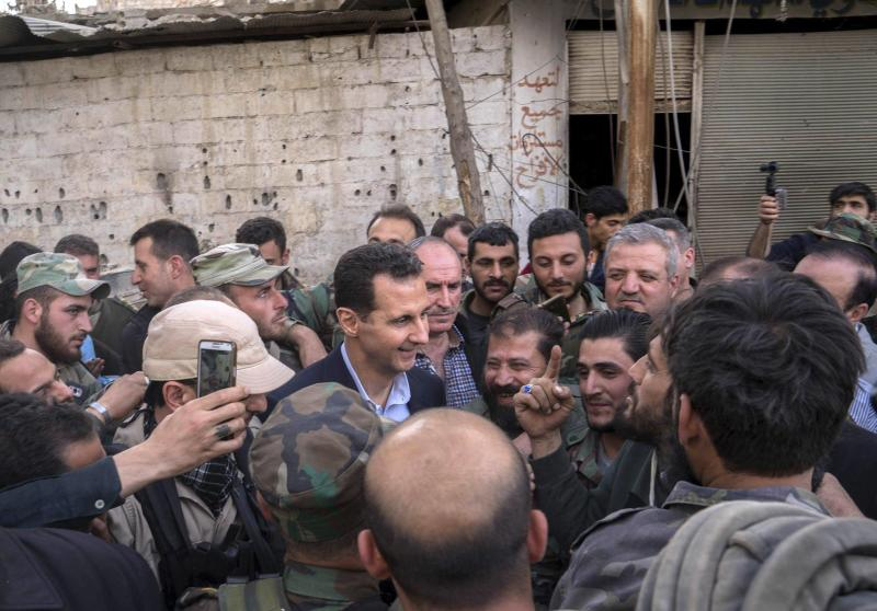 Syrian President Bashar Assad, center, speaks with Syrian troops near Damascus