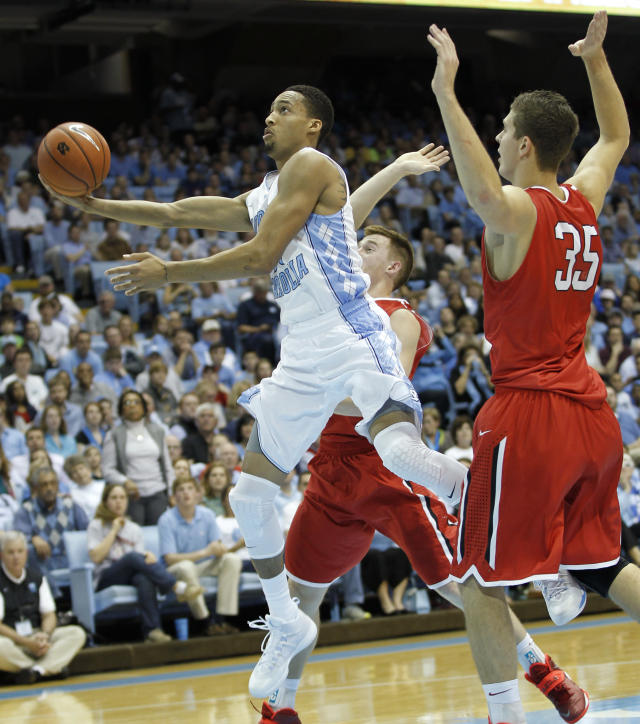 North Carolina's J.P Tokoto, center, goes to the basket against the defense of Davidson's Brian Sullivan, rear, and Chris Czerapowicz (35) during the first half of an NCAA college basketball game in Chapel Hill, N.C., Saturday, Dec. 21, 2013. (AP Photo/Ellen Ozier)
