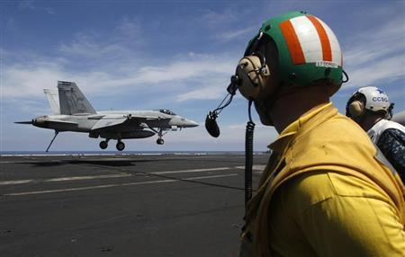 A U.S. Navy F/A 18 Hornet aircraft prepares its tailhook to catch an arresting wire in a landing maneuver during a tour of the USS Nimitz aircraft carrier on patrol in the South China Sea