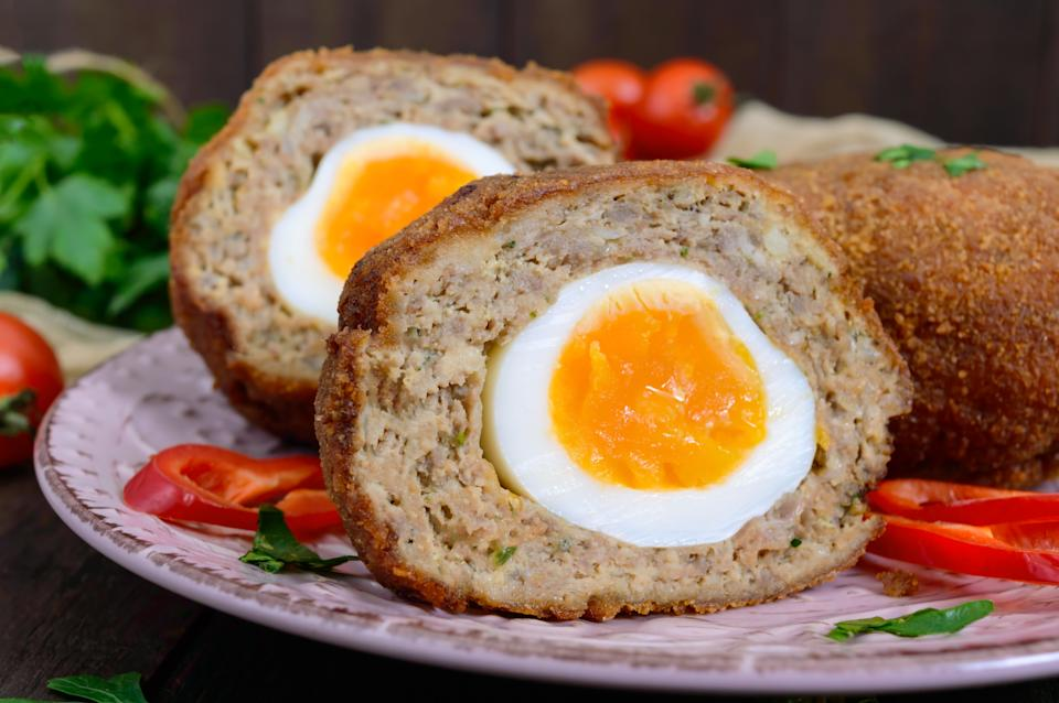 Large juicy cutlets stuffed with boiled egg on a dark wooden background. Scottish cutlet.