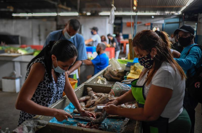 Vendors clean fish at the municipal market of Chacao in Caracas amid the COVID-19 novel coronavirus pandemic, on September 3, 2020 as inflation increases in Venezuela which is in the midst of the worst economic crisis in its history after seven years of recession. - Venezuela is sitting on the world's largest proven oil reserves but under Nicolas Maduro's watch, the country has descended into crisis. Poverty has soared, inflation is the highest in the world, the currency has become practically worthless, and oil production is down to its lowest level in 77 years, which experts blame on mismanagement and corruption. (Photo by Federico PARRA / AFP) (Photo by FEDERICO PARRA/AFP via Getty Images)