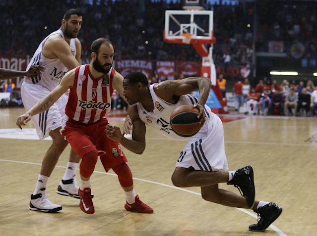 Olympiakos' Vassilis Spanoulis, center, defends as Real Madrid's Tremmell Darden, right, goes to score and Ioannis Bourousis looks on during a Euroleague playoff game 3 basketball match at the Peace and Friendship Arena in Athens' port of Piraeus on Monday, April 21, 2014. (AP Photo/Thanassis Stavrakis)