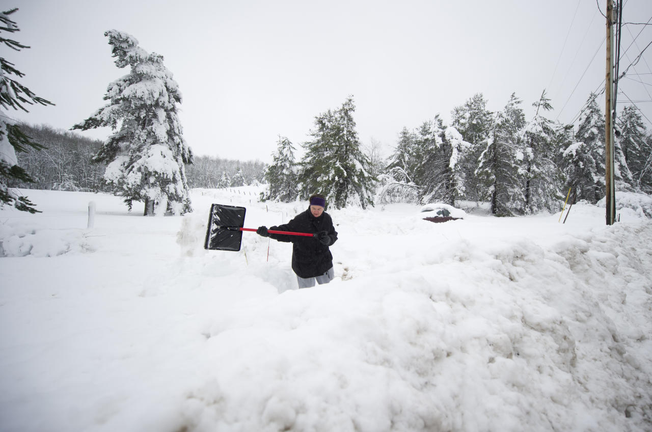 RandeeTharp, 47, clears deep snow to access Rt. 7 on October 31, 2012 in Hutton, Maryland.  Hurricane Sandy mixed with colder temperatures in higher elevations and dumped as much as 3 feet of snow in some places. (Photo by Jeff Swensen/Getty Images)