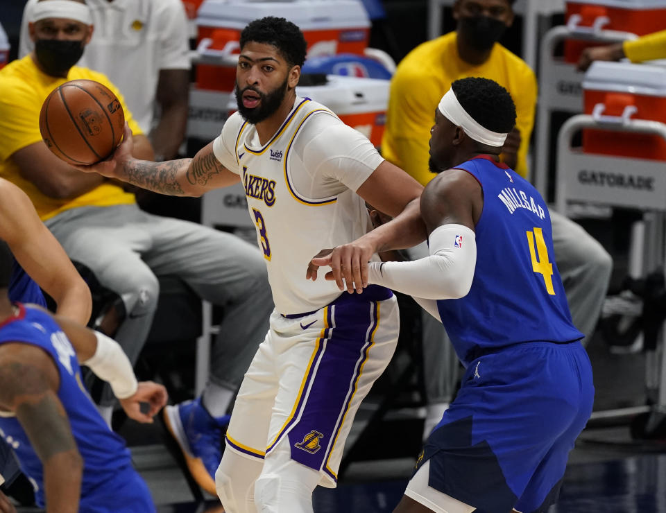 Los Angeles Lakers forward Anthony Davis (3) and Denver Nuggets forward Paul Millsap (4) in the first half of an NBA basketball game Sunday, Feb. 14, 2021, in Denver. (AP Photo/David Zalubowski)