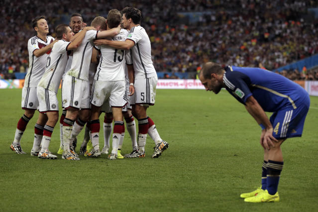 Germany's Mario Goetze (19) celebrates with teammates after scoring his side's first goal in extra time against Argentina's goalkeeper Sergio Romero during the World Cup final soccer match between Germany and Argentina at the Maracana Stadium in Rio de Janeiro, Brazil, Sunday, July 13, 2014. (AP Photo/Felipe Dana)