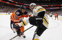 Boston Bruins' Noel Acciari (55) is checked by Edmonton Oilers' Kyle Brodziak (28) during first period NHL hockey action in Edmonton, Alberta, Thursday Oct. 18, 2018. (Jason Franson/The Canadian Press via AP)