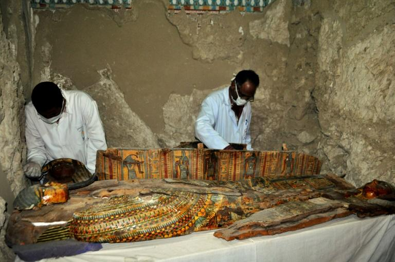 Members of an Egyptian archaeological team work on a wooden coffin discovered in a 3,500-year-old tomb in the Draa Abul Nagaa necropolis, near the southern Egyptian city of Luxor, on April 18, 2017
