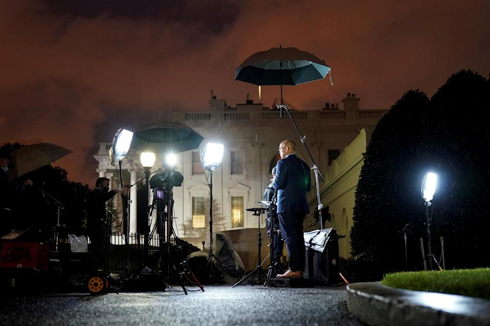Journalists report before dawn at the White House after U.S. President Donald Trump announced that he and U.S. first lady Melania Trump have both tested positive for the coronavirus disease (COVID-19) in Washington, U.S., October 2, 2020. REUTERS/Joshua Roberts TPX IMAGES OF THE DAY