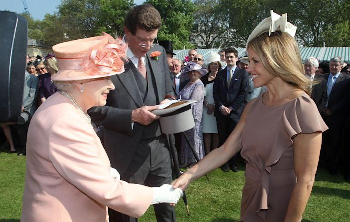 <p> Hundreds of onlookers watched as Queen Elizabeth welcomed journalist Katie Couric to her Buckingham Palace Garden Party, for which she was dressed in a mauve shift dress and white fascinator. </p>