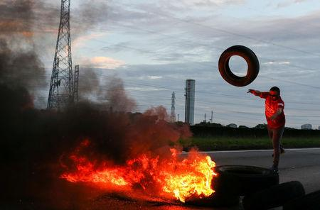 A protestor throws a tire into a bonfire to block the Presidente Dutra highway during a strike against Brazilian Social Welfare reform project from government, in Sao Jose dos Campos