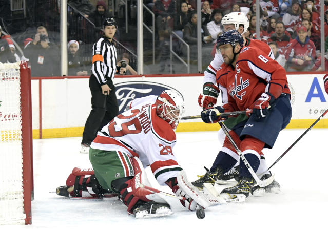New Jersey Devils goaltender Mackenzie Blackwood (29) deflects a shot as Washington Capitals left wing Alex Ovechkin (8) skates in during the first period of an NHL hockey game Friday, Dec. 20, 2019, in Newark, N.J. (AP Photo/Bill Kostroun)