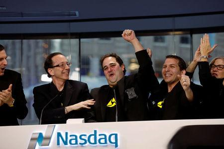 Josh Isner, (C) Executive Vice President of Global Sales and Representatives of Axon (formerly known Taser International Inc.) ring the closing bell at the Nasdaq MarketSite in New York City, U.S., April 5, 2017. REUTERS/Brendan McDermid