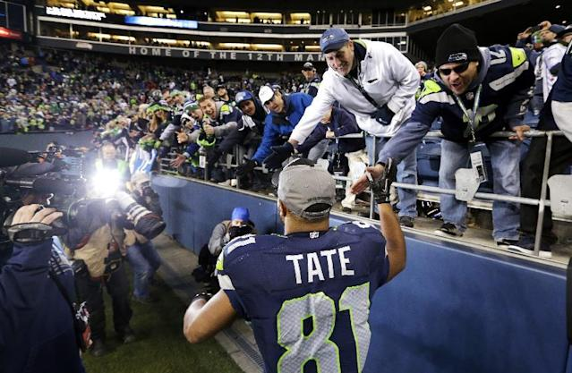 Seattle Seahawks' Golden Tate greets fans as he leaves the field after the team beat the St. Louis Rams in an NFL football game, Sunday, Dec. 29, 2013, in Seattle. The Seahawks won 27-9. (AP Photo/Elaine Thompson)