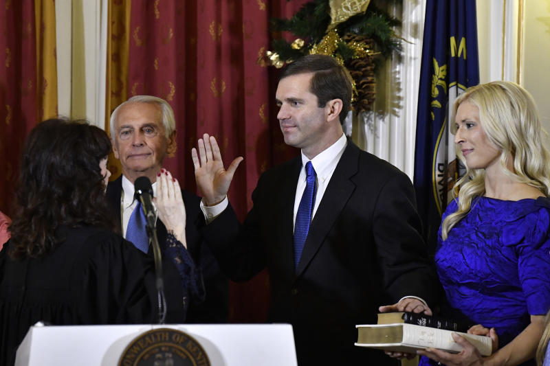 Kentucky Supreme Court Justice Michelle M. Keller, left, gives the oath of office to Andy Beshear to become Kentucky's governor in Frankfort, Ky., early Tuesday, Dec. 10, 2019. Holding the Bible is Beshear's wife, Britainy. (AP Photo/Timothy D. Easley, Pool)