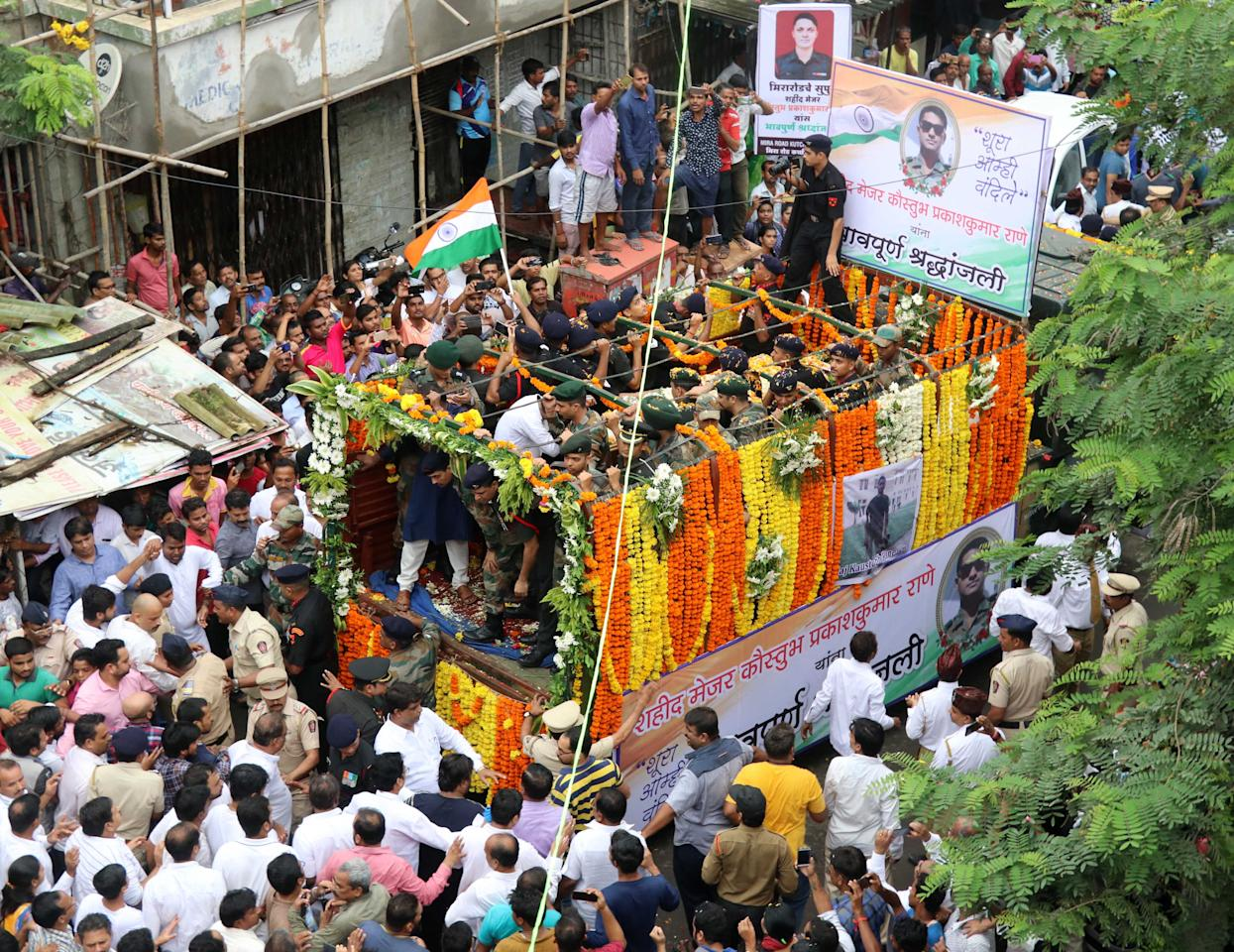 <p>The funeral procession of Indian Army Major Kaustubh Rane, who was killed in a gun battle Tuesday in Kashmir, moves past standing public in Mumbai, India, Thursday, Aug 9, 2018. (Yahoo India/Stringer) </p>
