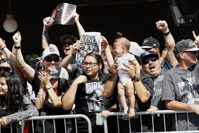 Los Angeles Kings cheer as their team parades with the Stanley Cup trophy downtown Los Angeles, Monday, June 16, 2014. The parade and rally were held to celebrate the Los Angeles Kings' second Stanley Cup championship in three seasons. (AP Photo/Nick Ut)