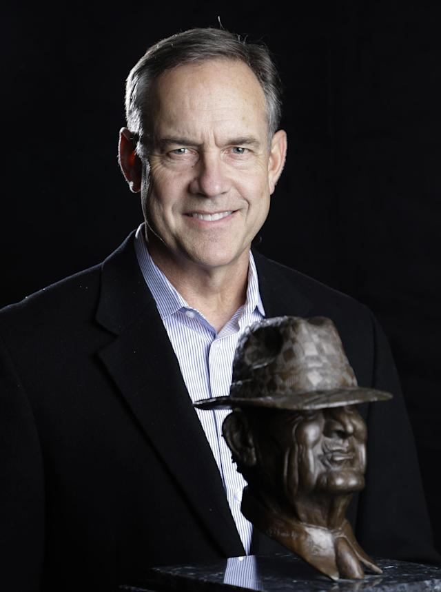 """Michigan State coach Mark Dantonio, a finalist for the Paul """"Bear"""" Bryant college coach of the year award, poses with the trophy Wednesday, Jan. 15, 2014, in Houston. (AP Photo/Pat Sullivan)"""