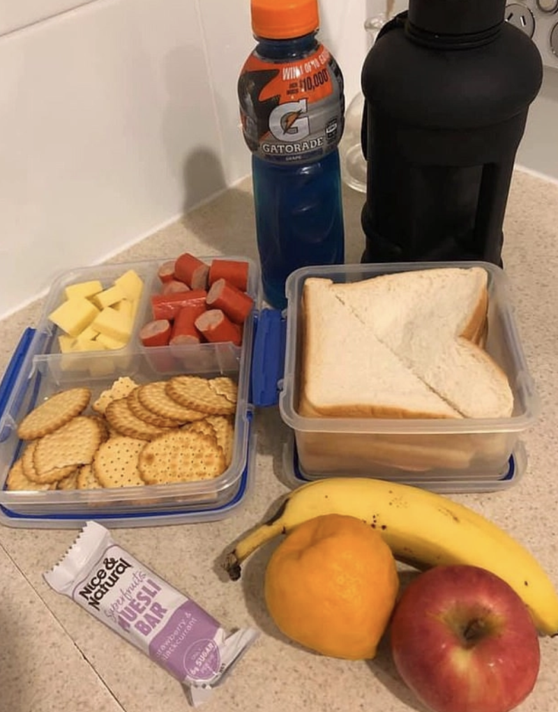 A sandwich in a lunchbox, fruit, Gatorade, sliced cheese and a muesli bar are pictured.
