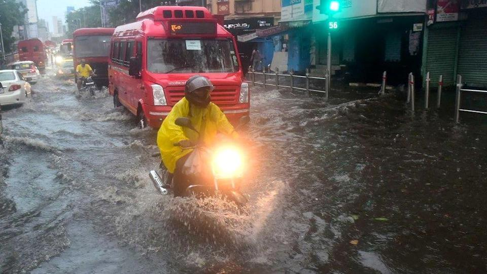 People deal with the water clogging in the wake of Cyclone Tauktae at Dadar TT circle on May 17, 2021 in Mumbai, India.