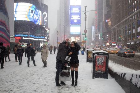People take a selfie in Times Square on a snowy day in New York City