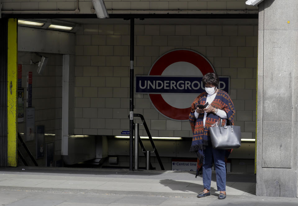 A woman wears a protective mask as she waits outside a tube station in London, as the country is in lockdown to help curb the spread of the coronavirus, Monday, April 13, 2020. The new coronavirus causes mild or moderate symptoms for most people, but for some, especially older adults and people with existing health problems, it can cause more severe illness or death. (AP Photo/Kirsty Wigglesworth)
