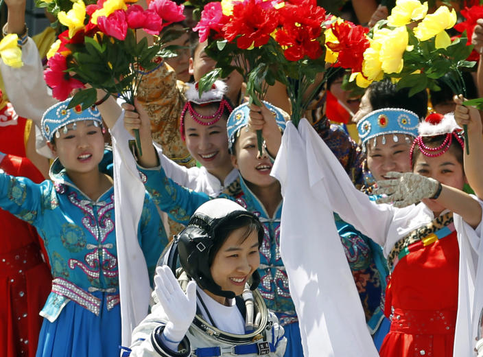 FILE - In this file photo taken Saturday, June 16, 2012, China's first female astronaut Liu Yang, bottom, waves during a sending off ceremony as she departs for the Shenzhou 9 spacecraft rocket launch pad at the Jiuquan Satellite Launch Center in Jiuquan, China. A glance at history suggests it's easier for a Chinese woman to orbit Earth than to land a spot on the highest rung of Chinese politics. In June, the 33-year-old Air Force major marked a major feminist milestone by becoming the first Chinese woman to travel in space. With a once-a-decade leadership transition set to kick off Nov. 8, many now are waiting to see if another ambitious Chinese female, State Councilor Liu Yandong, can win one of the nine spots at the apex of Chinese power.(AP Photo/Ng Han Guan, File)