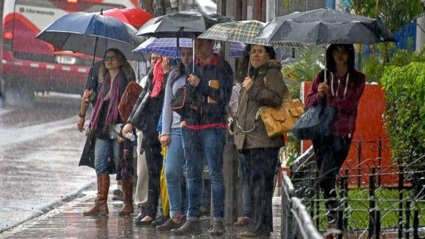 PHOTO: Locals holding umbrellas wait at a bus stop during a downpour caused by tropical storm Nate in Cartago, Costa Rica, Oct. 5, 2017. (Ezequiel Becerra/AFP/Getty Images)