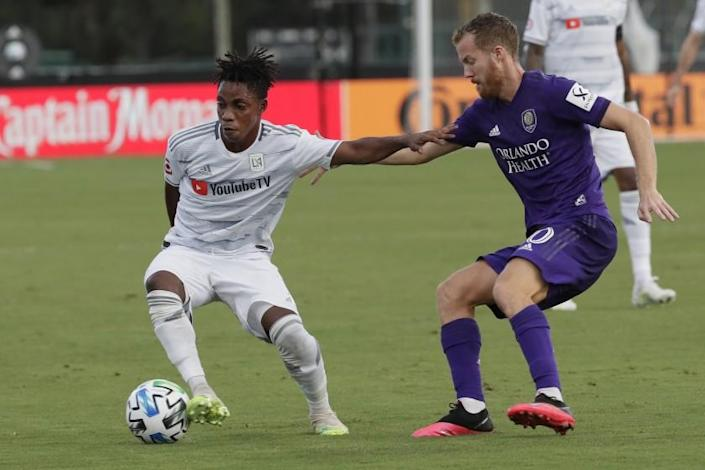 """LAFC's Latif Blessing, left, tangles with Orlando City's Oriol Rosell on July 31 in Orlando. <span class=""""copyright"""">(John Raoux / Associated Press)</span>"""