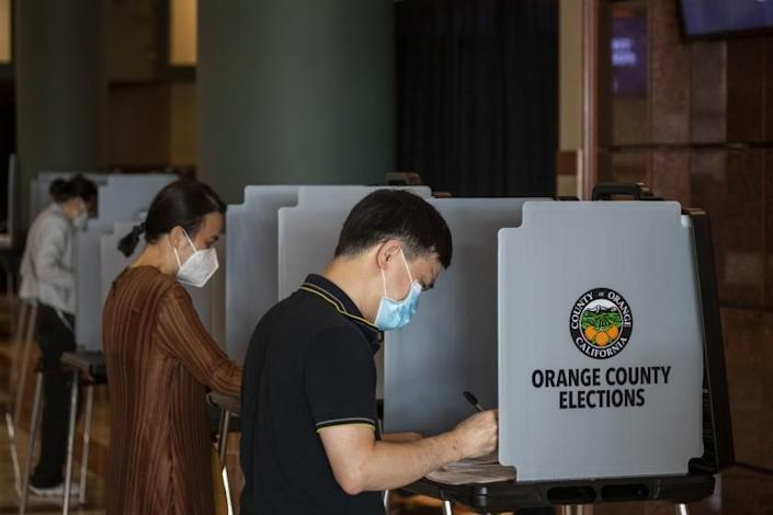 ANAHEIM, CA - NOVEMBER 02: From left: Minh Hien Nguyen, Krissy Nguyen, and her husband Quan Nguyen, all of Santa Ana, vote early in the General Election at the Honda Center in Anaheim Monday, Nov. 2. (Allen J. Schaben / Los Angeles Times)