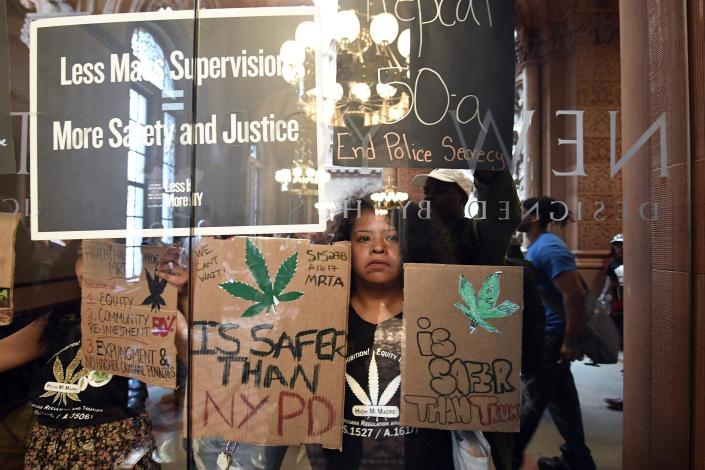 Pilar DeJesus with a coalition of protesters urging legislators to pass Marijuana legislation holds a sign against the senate lobby doors at the state Capitol Wednesday, June 19, 2019, in Albany, N.Y. (AP Photo/Hans Pennink)
