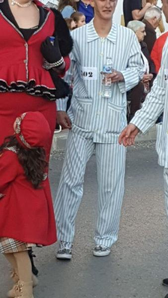 A person disguised as a concentration camp prisoner walks during a carnival parade in Campo De Criptana