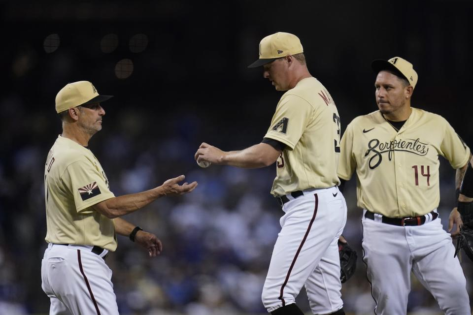 Arizona Diamondbacks manager Torey Lovullo, left, takes the ball from relief pitcher Joe Mantiply, middle, as third baseman Asdrubal Cabrera (14) waits during the eighth inning of the team's baseball game against the Los Angeles Dodgers on Friday, June 18, 2021, in Phoenix. The Dodgers won 3-0. (AP Photo/Ross D. Franklin)