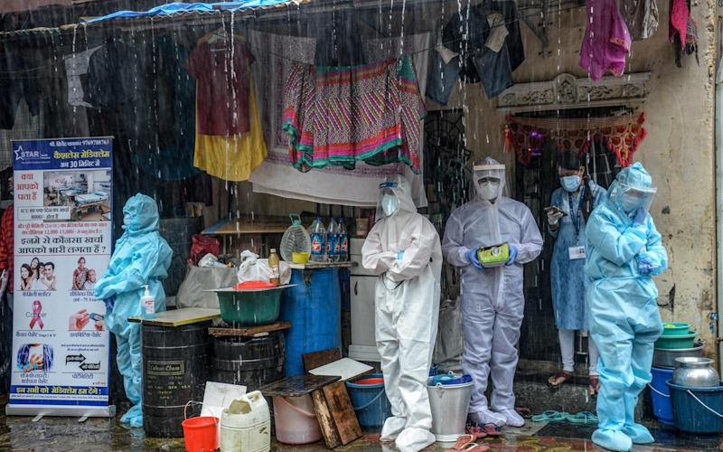 Health workers wearing Personal Protective Equipment (PPE) suits take shelter while conducting a COVID-19 coronavirus screening under heavy rain in Mumbai on August 12 - INDRANIL MUKHERJEE/AFP