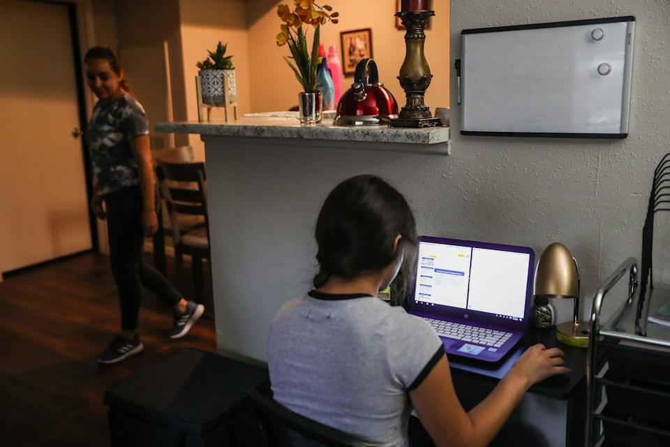 Jacqueline Aviña, 15, checks her homework for the week from her school at home as her mother, Alma Vargas, does chores in May. Preliminary schedules indicate students will have the choice between in-person, virtual or hybrid learning.