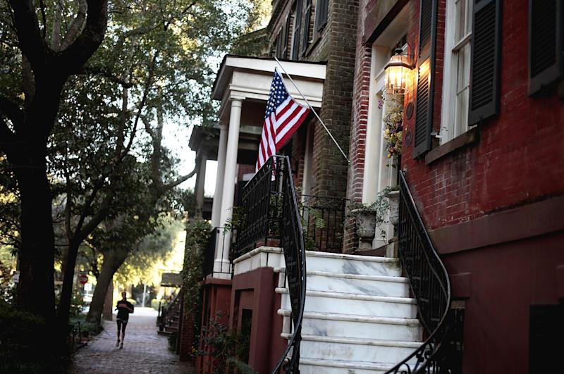 In this Feb. 21, 2011 photo, a U.S. flag decorates the front door of a home in the historic district of Savannah, Ga. A proposal to roll out double-decker buses on the streets of historic downtown Savannah has residents complaining the change would amount to a tourism overload. Two Boston businessmen are lobbying Savannah City Hall to end a 17-year ban on double-decker buses in the downtown historic district of Georgia's oldest city. The city's Downtown Neighborhood Association is opposing the change. Its members say the buses would risk collisions with low-hanging tree limbs and would turn passengers into Peeping Toms capable of peering into second-story windows. (AP Photo/David Goldman)
