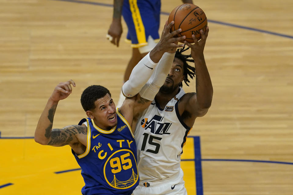 Golden State Warriors forward Juan Toscano-Anderson (95) reaches for the ball next to Utah Jazz center Derrick Favors (15) during the first half of an NBA basketball game in San Francisco, Monday, May 10, 2021. (AP Photo/Jeff Chiu)
