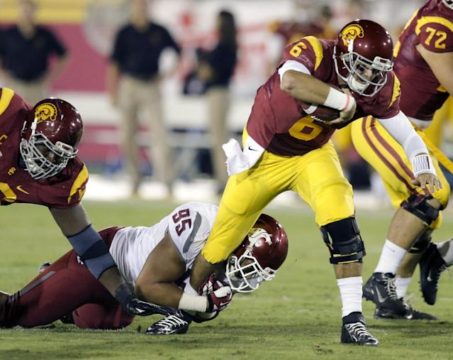 Southern California quarterback Cody Kessler, right, is tackled by Washington State nose tackled Ioane Gauta during the first half of an NCAA college football game in Los Angeles, Saturday, Sept. 7, 2013. (AP Photo/Chris Carlson)
